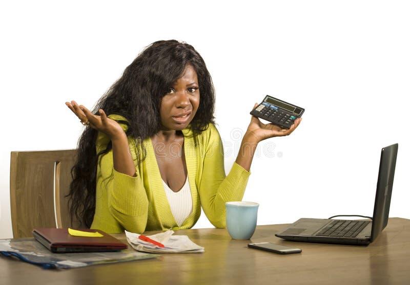Den unga stressade och frustrerade kvinnan som arbetar hemmastadd redovisning för skrivbord för kontorsdator, uppta som omkostnad royaltyfria bilder