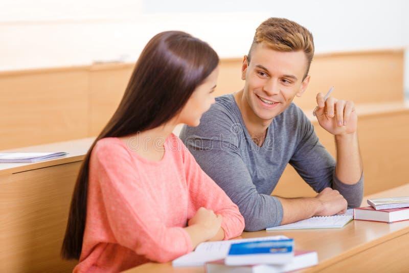 Den unga studenten pratar med hans klasskompis fotografering för bildbyråer