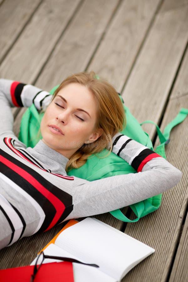 Den unga studenten vilar att ligga på träetapp royaltyfria foton