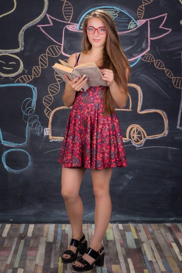 Den unga studentflickan i röd klänning står och läser boken royaltyfri foto