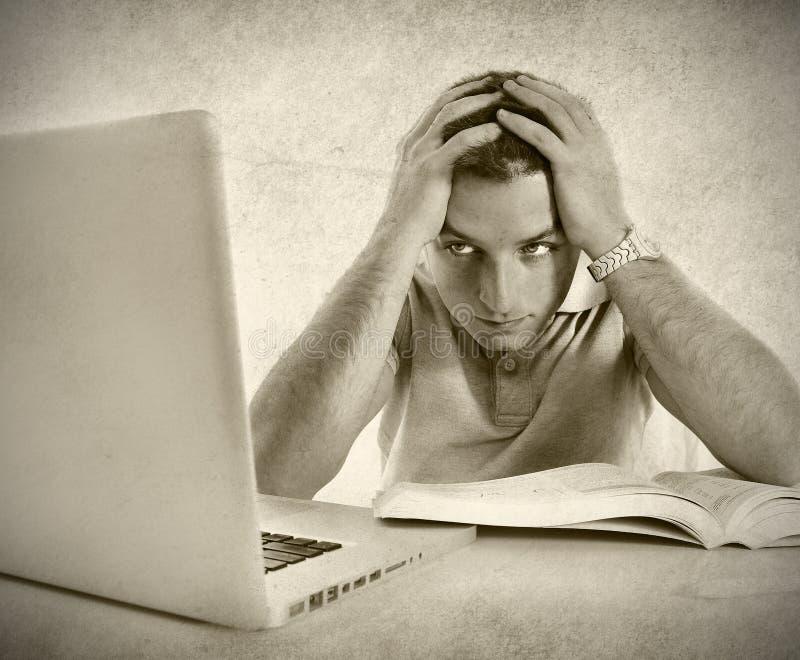 Den unga studentmannen i spänning förkrossade att studera examen med boken och datoren royaltyfria bilder