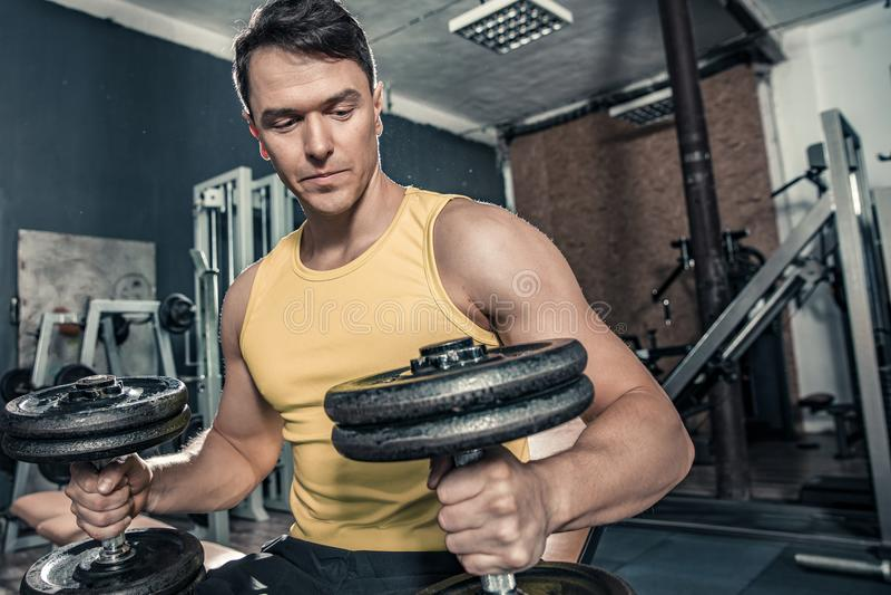 Den unga sunda mannen förbereder sig att lyfta hantlar på idrottshallen fotografering för bildbyråer