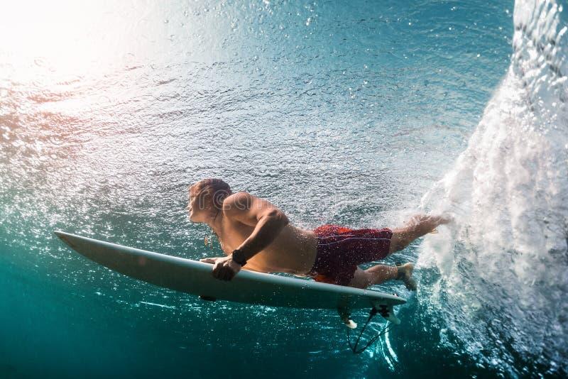 Den unga surfaren dyker under havvågen royaltyfri bild