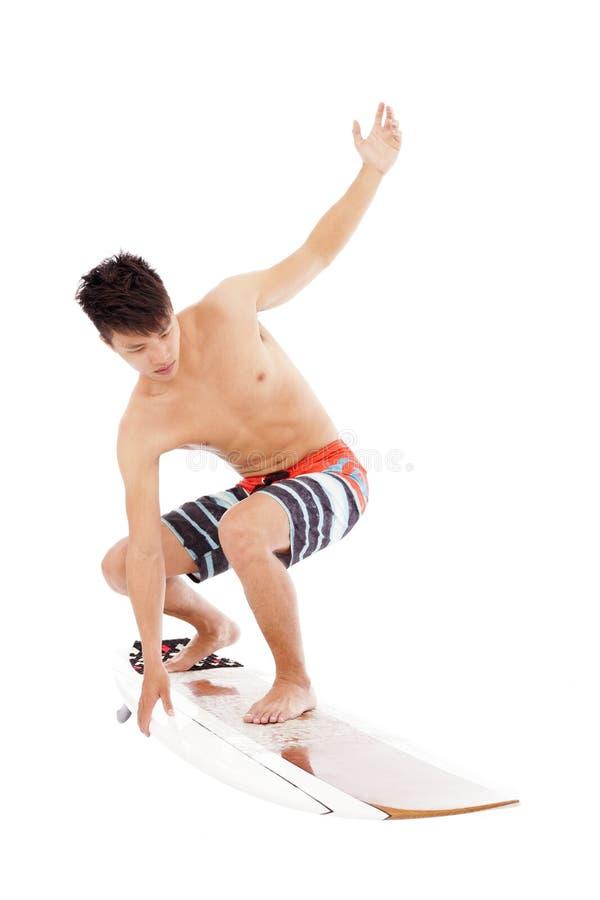 Den unga surfaren gör surfa posera arkivfoto
