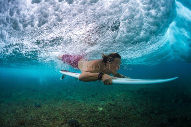 Den unga surfaren gör tricket namngav Duck Dive royaltyfria foton
