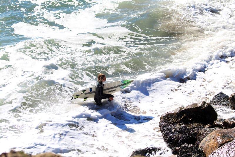 Den unga surfaren med bränningbrädet går ut ur vatten till det ohyfsat vaggar kusten på en fjärd i San Francisco royaltyfri foto