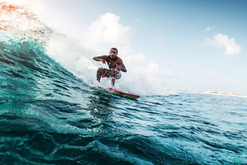 Den unga surfaren rider vågen royaltyfria foton