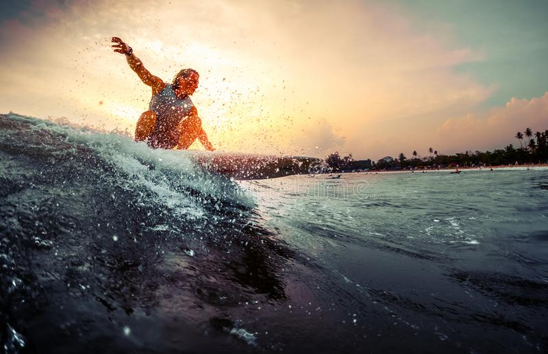 Den unga surfaren rider vågen arkivfoton