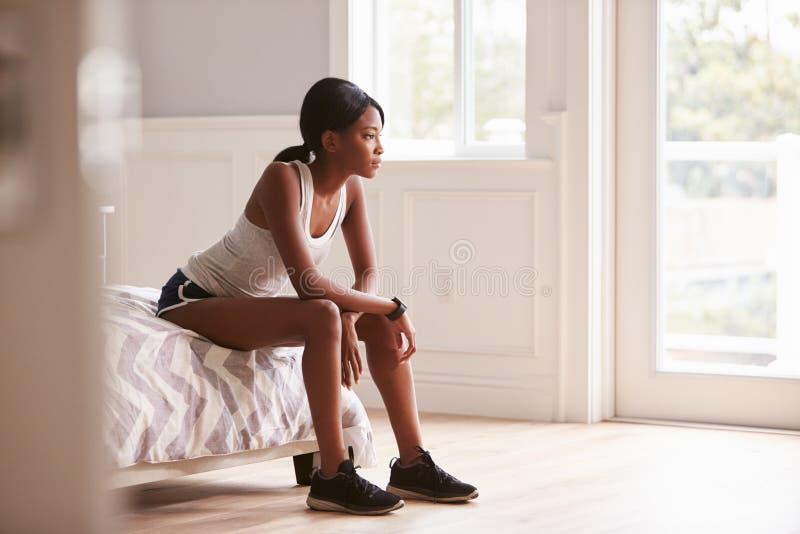 Den unga svarta kvinnan i sportar beklär sammanträde på säng hemma arkivfoto
