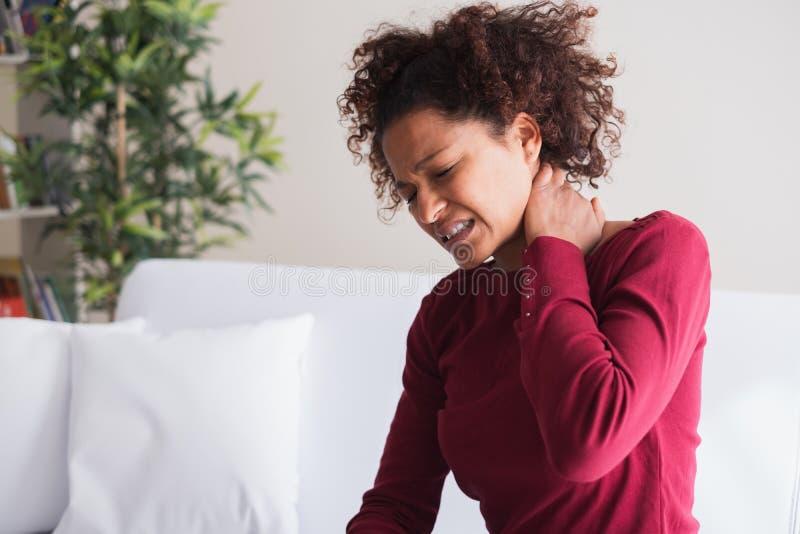 Den unga svarta kvinnan lider skuldran, och halsen smärtar royaltyfri foto