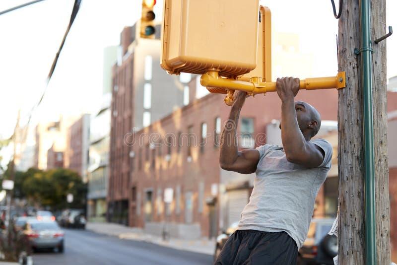 Den unga svarta mannen som gör hakan, ups från korsning ljus i gata royaltyfri fotografi