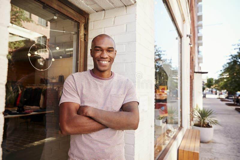 Den unga svarta mannen som ler till kameran utanför hans kläder, shoppar royaltyfri foto