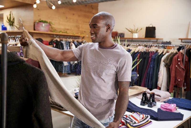 Den unga svarta mannen som ser kläder i kläder, shoppar royaltyfria foton