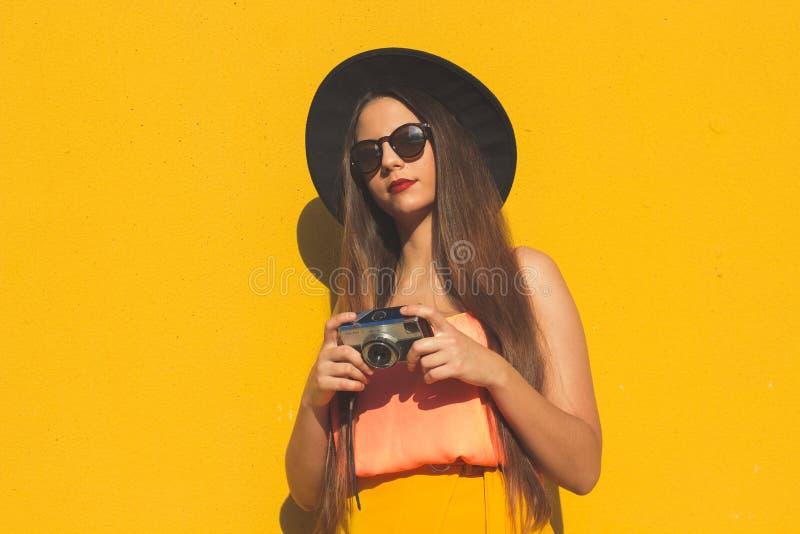 Den unga tappningflickan som använder en retro fotokamera och bär trendig solglasögon och en svart hatt arkivfoton