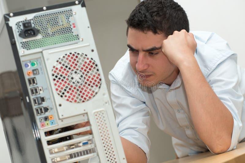 Den unga teknikeren har ett problem med datoren arkivfoto