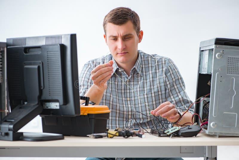 Den unga teknikeren som reparerar datoren i seminarium royaltyfri fotografi
