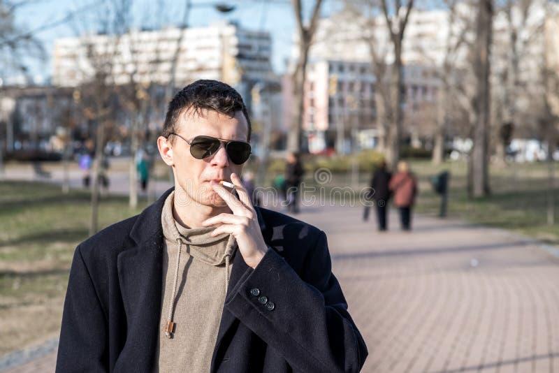 Den unga tillfälliga rökaremannen med solglasögon i det svarta laget som röker cigaretten utanför i, parkerar arkivbilder