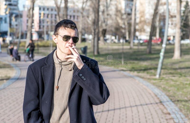 Den unga tillfälliga rökaremannen med solglasögon i det svarta laget som röker cigaretten utanför i, parkerar arkivfoton