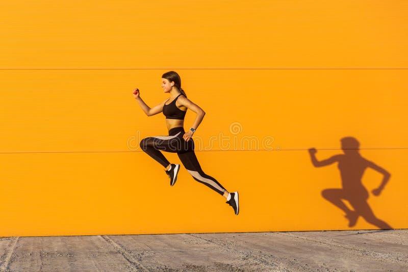 Den unga tillfredsställda sportiga härliga kvinnan med den färdiga kroppen som hoppar och kör, skynda sig upp mot orange väggbakg royaltyfri bild