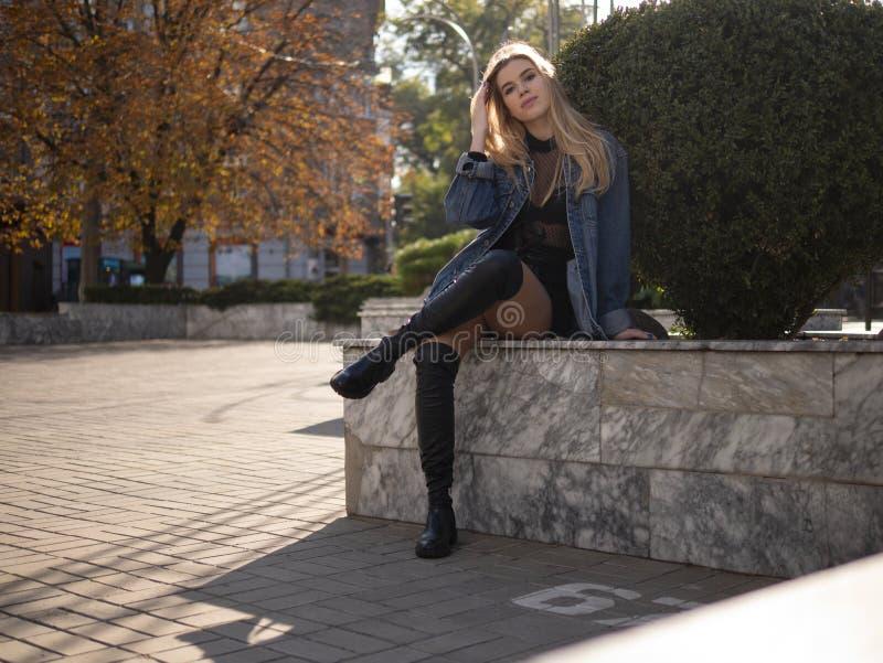 Den unga tonåriga flickan med brunn-ansat hår med härliga långa ben sitter på gatan med hennes korsade ben royaltyfri fotografi