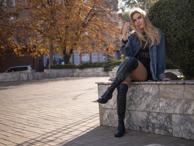 Den unga tonåriga flickan med brunn-ansat hår med härliga långa ben sitter på gatan med hennes korsade ben arkivbilder