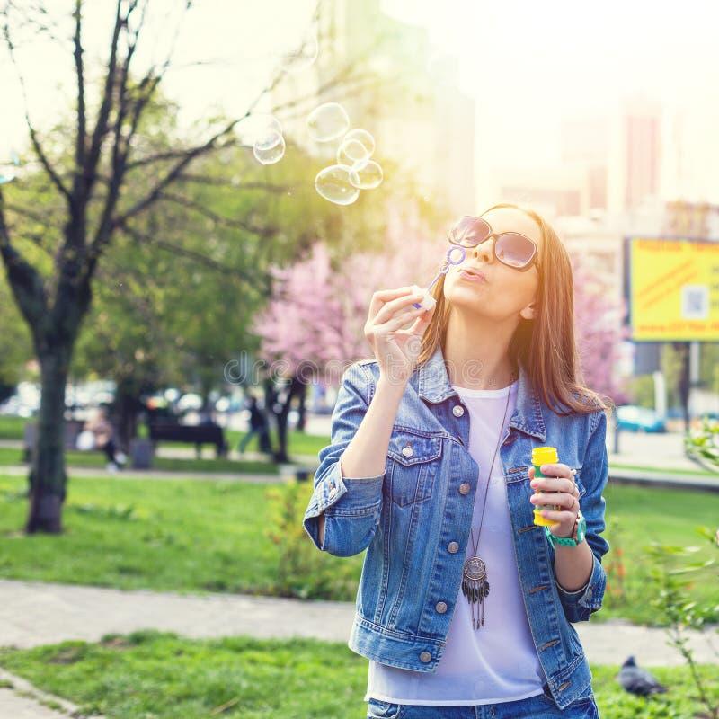 Den unga tonåriga flickan som har gyckel i stad, parkerar utomhus- royaltyfri foto