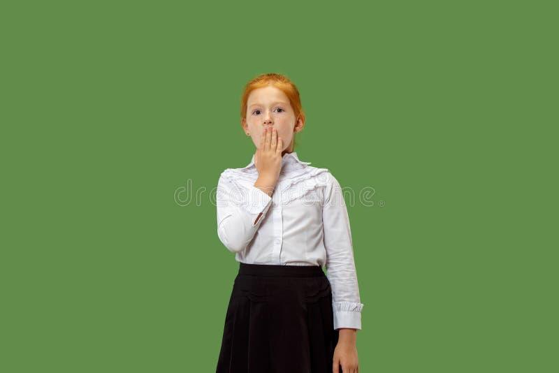 Den unga tonåriga flickan som viskar en hemlighet bak hennes hand över grön bakgrund royaltyfri fotografi