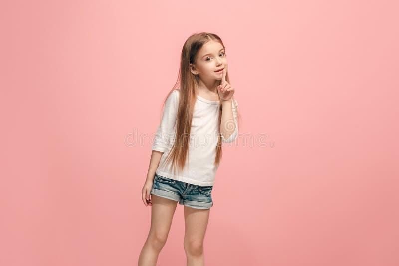 Den unga tonåriga flickan som viskar en hemlighet bak hennes hand över rosa bakgrund royaltyfria bilder