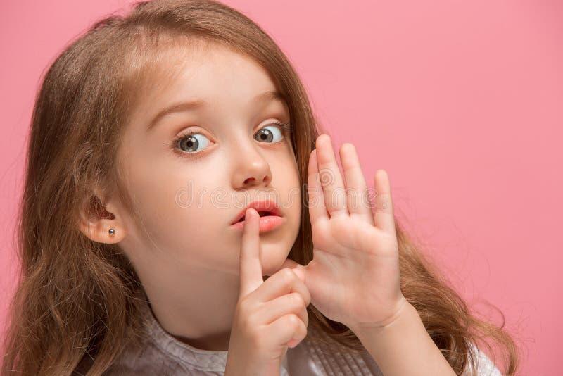 Den unga tonåriga flickan som viskar en hemlighet bak hennes hand över rosa bakgrund royaltyfri foto