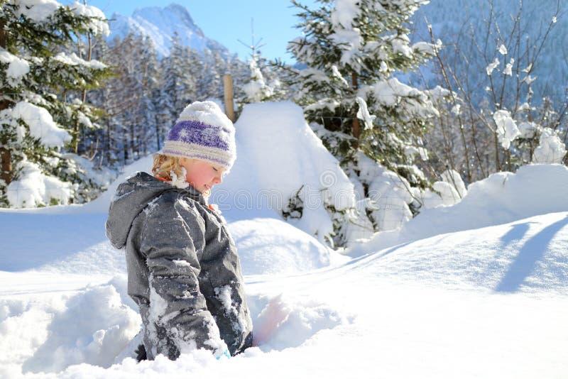 Den unga tonåringen spelar i snö royaltyfria bilder
