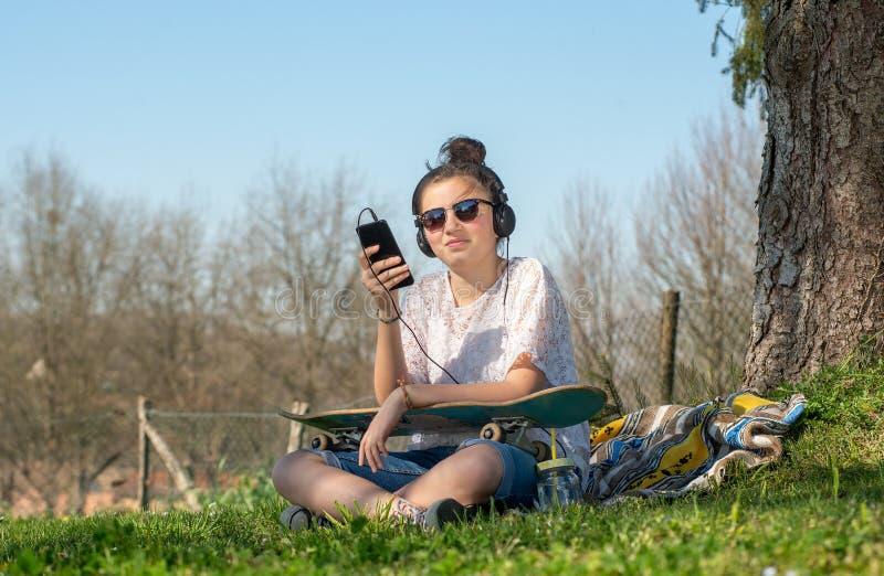 Den unga tonåringflickan med lyssnande musik för solglasögon i parkerar royaltyfri foto