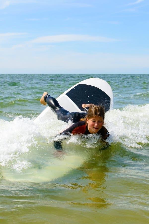 Den unga tonårs- flickan har gyckel på semester med att surfa kurser arkivfoto