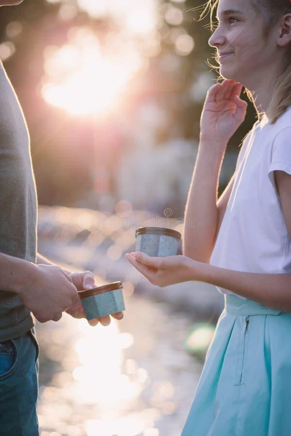 Den unga tonårs- flickan och pojken som spenderar tid i stadsmitten, tycker om tillsammans att äta glass på en sommardag Utgifter arkivbilder