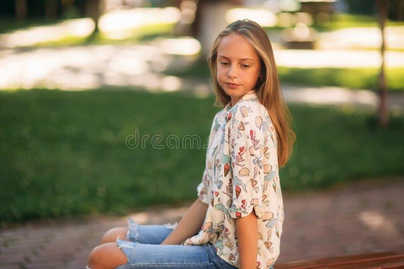 Den unga tonårs- flickan sitter på bänken arkivbild