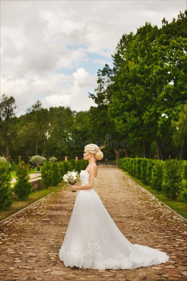 Den unga trendiga bruden, härlig blond modellflicka med den stilfulla bröllopfrisyren, i vit snör åt klänningen som utomhus poser royaltyfri foto
