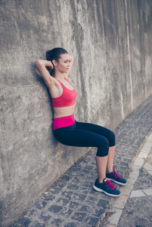 Den unga trendiga idrottskvinnan sträcker på gatan på ett s arkivfoton