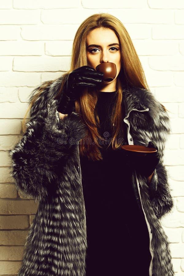Den unga trendiga sexiga nätta rika kvinnan med härligt långt blont hår i midjalag av grå färger pälsfodrar med svart läder royaltyfria bilder