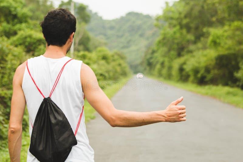 Den unga turisten på den hitckhiking kvinnan för vägen röstar på vägen H?rlig flicka p? v?gen En man går på semester, stoppar bil royaltyfri foto