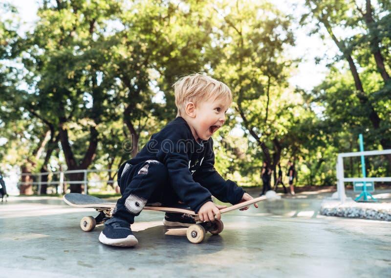 Den unga ungen som sitter i, parkerar på en skateboard arkivfoto
