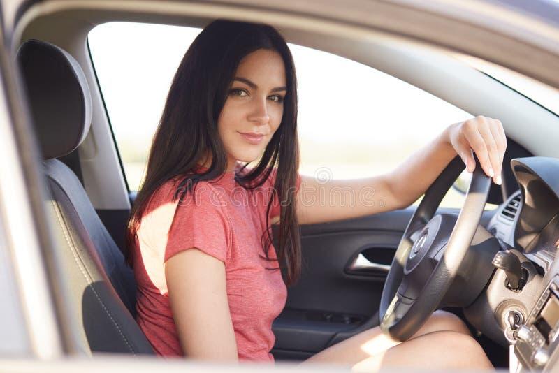 Den unga ursnygga brunettdamen kör bilen bara, ser säkert på kameran, uppehällehanden på hjulet, något liknande som reser med bil royaltyfria bilder