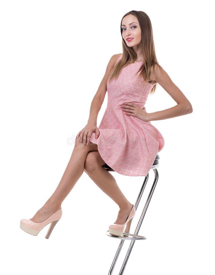 Den unga ursnygga caucasian kvinnan i rosa färger klär på stolen arkivbilder