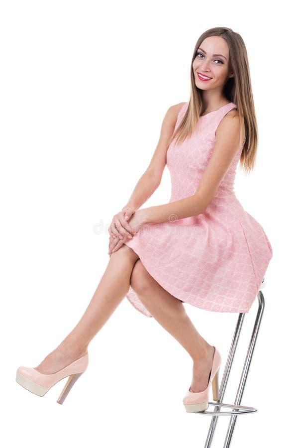 Den unga ursnygga caucasian kvinnan i rosa färger klär på stolen fotografering för bildbyråer