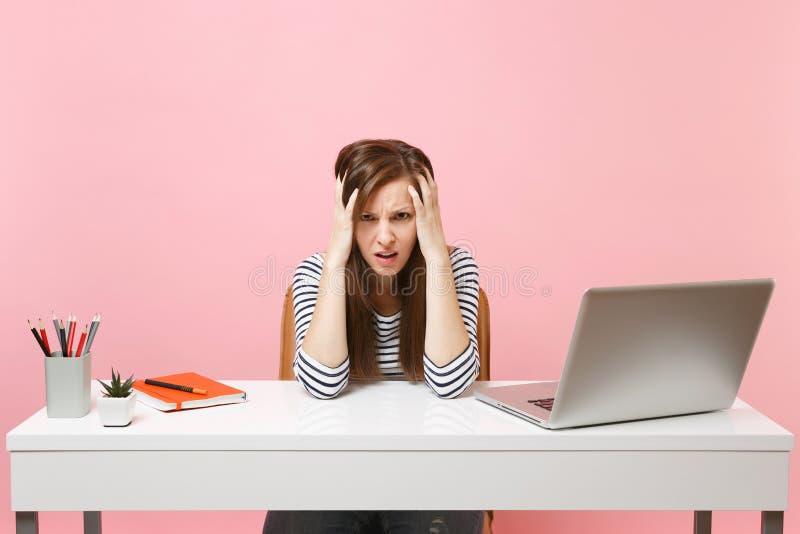 Den unga utmattade ledsna kvinnan som har problem som klamra sig fast intill huvudet, sitter och arbetar på det vita skrivbordet  fotografering för bildbyråer