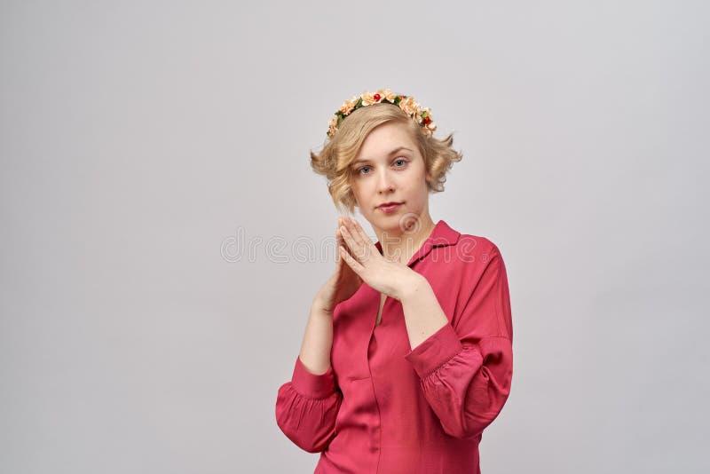 Den unga uttrycksfulla blonda kvinnan i röd klänning med lockigt hår stirrar på kameran med händer knäppte fast framme av henne fotografering för bildbyråer