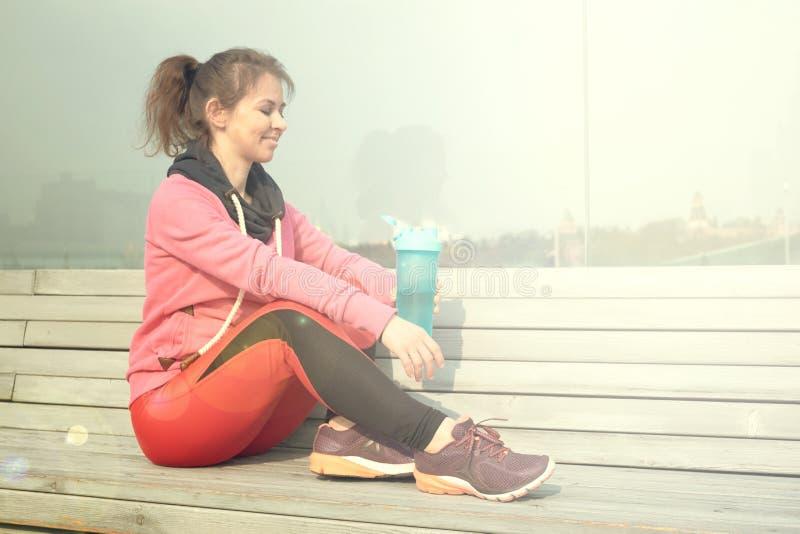 Den unga vanliga kvinnan dricker vatten vilar, når han har joggat i ottan starta dagen med sportar arkivfoto