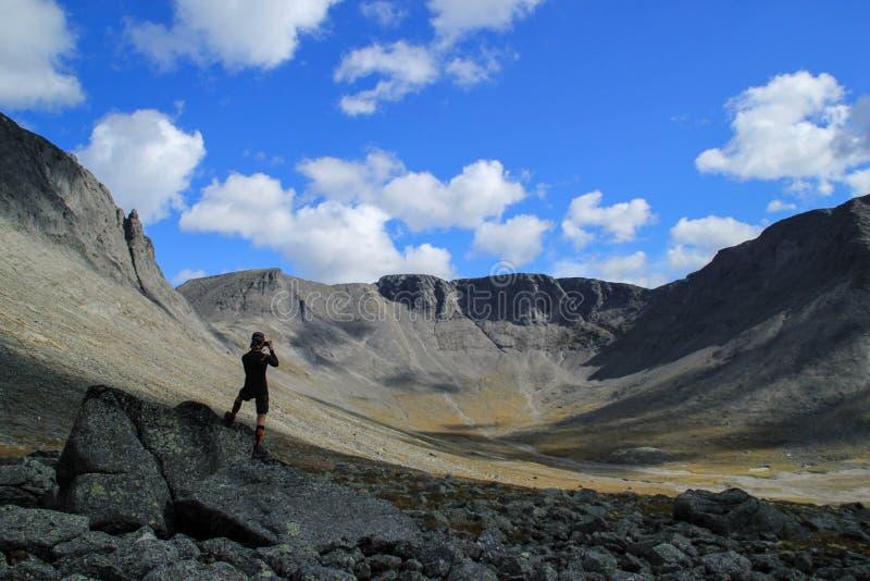 Den unga vita Caucasian manliga turisten tar fotoet av härliga berg arkivfoton