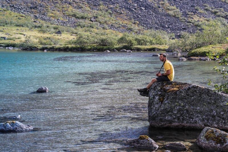 Den unga vita Caucasian mannen med en obetydlig orakad gul ärmlös tröja sitter på en sten på kusten royaltyfria foton
