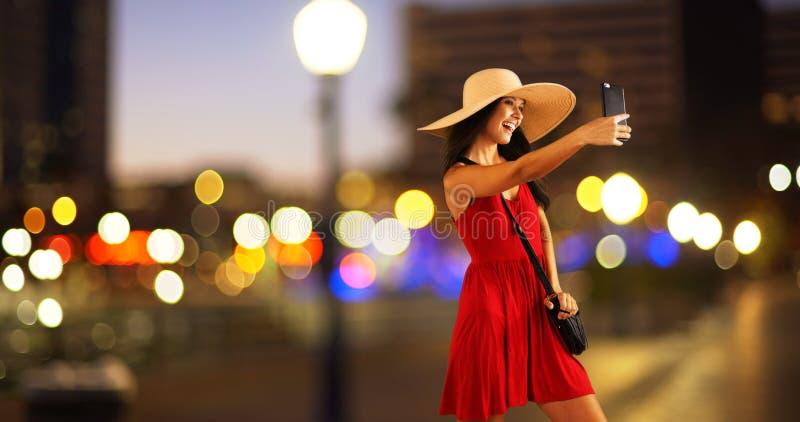 Den unga vita flickan tar selfies i city royaltyfri foto