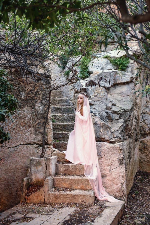 den unga vita häxadrottningen klättrar stenmomenten av en sagatrappuppgång i en lång klänning och en diadem med en skyla arkivbilder