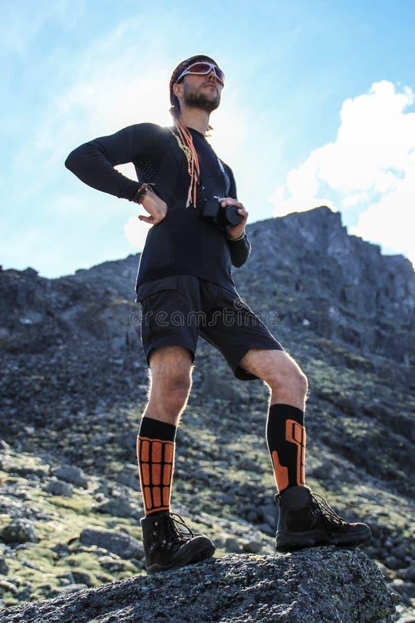 Den unga vita manliga turisten i sportswear och kängor som står på, vaggar i bergen arkivfoton